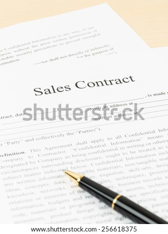 Sales contract document with pen, document is mock-up - stock photo
