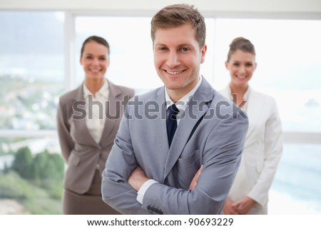Sales manager standing with arms folded and his team behind him