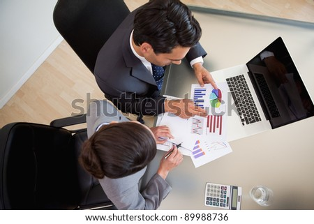 Sales persons studying statistics in an office - stock photo