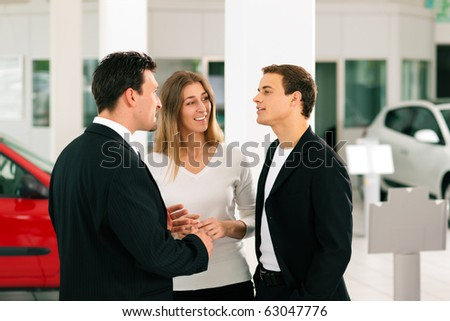 Sales situation in a car dealership, the dealer is talking to a young couple, there are cars standing in the background