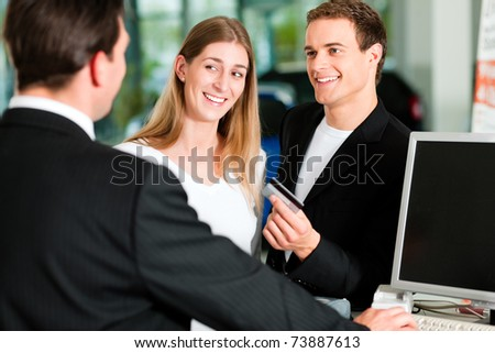Sales situation in a car dealership, the young couple is giving the credit card to pay for the new car - stock photo