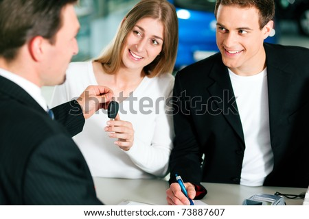 Sales situation in a car dealership, the young couple is signing the sales contract and gets the key for the new car - stock photo