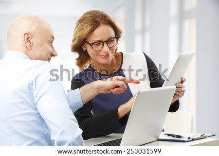 Sales team discussing new project while sitting at desk at office.  - stock photo