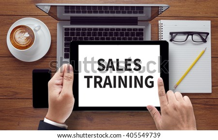 SALES TRAINING, on the tablet pc screen held by businessman hands - online, top view - stock photo