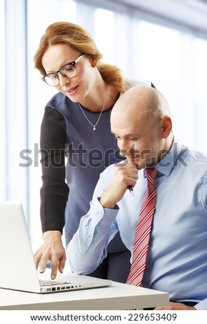 Sales woman and sales man working together on laptop while sitting at office. Business people.
