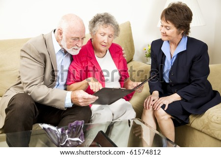 Sales woman looks on as a senior couple considers her product information. - stock photo
