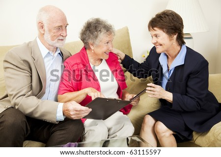 Sales woman making an aggressive pitch to a senior couple.  The husband is skeptical. - stock photo