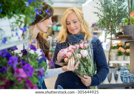 Sales woman showing flower bouquet to female customer at store - stock photo