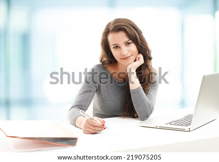 Sales woman working on laptop, while sitting at office.