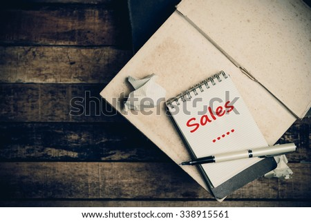 Sales word on pages sketch book on wood table vertical