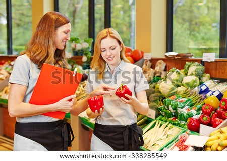 Salesclerk in training getting help from staff in a supermarket - stock photo