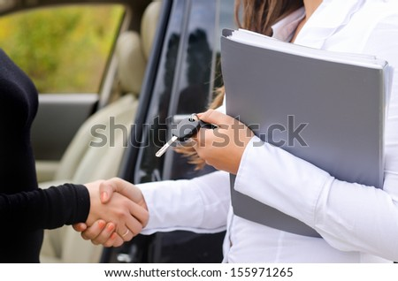 Saleslady selling a car to a new female owner and shaking hands to close the deal and congratulate her client while holding the paperwork and keys - stock photo