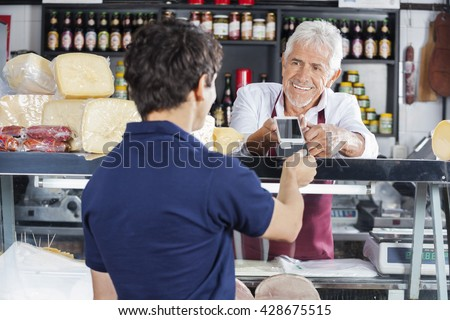 Salesman Accepting Payment From Customer In Cheese Shop - stock photo