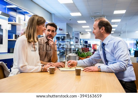 Salesman asking young couple to sign the sale receipt in electronics store - stock photo