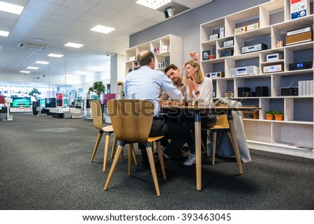 Salesman assisting young couple at counter in electronics shop - stock photo
