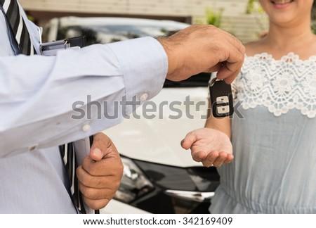 salesman automotive dealer offering cars key to buyer. - stock photo