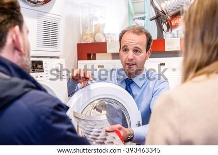 Salesman explaining product to couple in washing machine department of hypermarket - stock photo