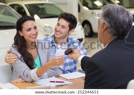 Salesman giving car keys to a couple at new car showroom - stock photo