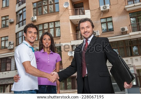 Salesman giving handshake to property owners. Handshake deal with young couple outside - stock photo