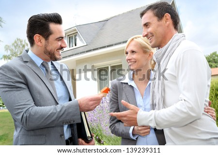 Salesman giving home keys to property owners - stock photo