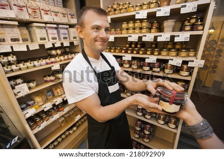 Salesman giving jar of jam to female customer in grocery store - stock photo