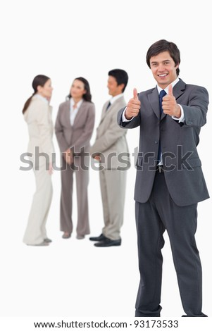 Salesman giving thumbs up with colleagues behind him against a white background