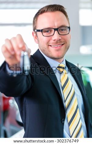 Salesman handing over auto key at car dealership - stock photo
