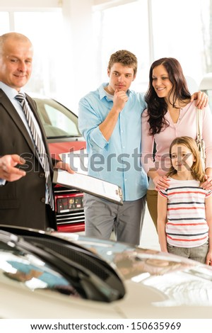 Salesman offering a family car to young couple - stock photo
