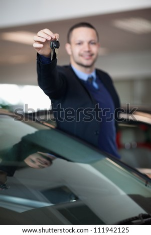 Salesman raising his arm while holding car keys in a dealership - stock photo