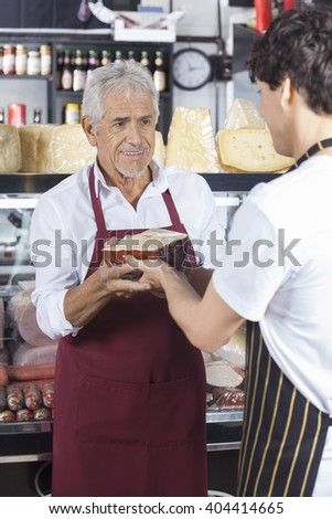 Salesman Receiving Cheese From Colleague In Grocery Shop - stock photo