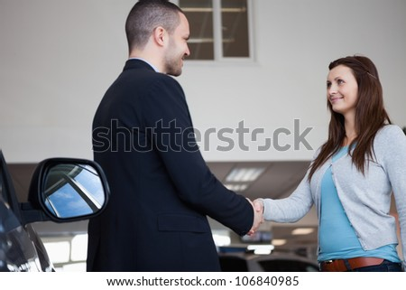 Salesman shaking hand of a client in a garage