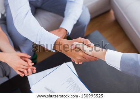 Salesman shaking hands with client with contract on the coffee table - stock photo