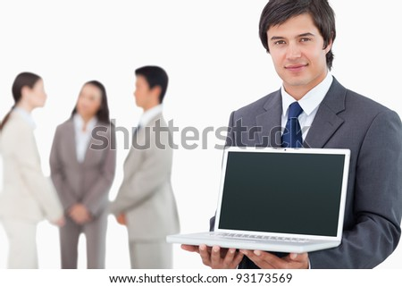 Salesman showing laptop screen with colleagues behind him against a white background