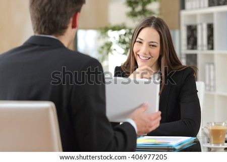 Salesman showing product from a tablet to a happy client who is looking at device in an office indoor - stock photo