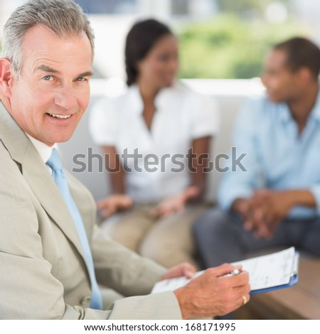 Salesman smiling at camera with couple behind him in the office