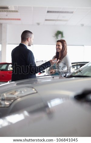 Salesman speaking with a woman in a dealership - stock photo