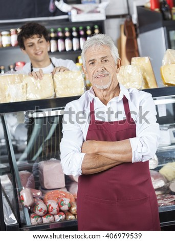 Salesman Standing Arms Crossed While Colleague Working At Counte - stock photo