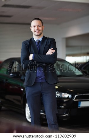 Salesman standing in front of car in a dealership