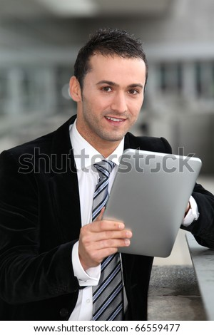 Salesman standing oustide with electronic tablet - stock photo