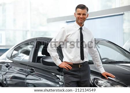 Salesman Stands Near Brand New Car. Car Showroom - stock photo