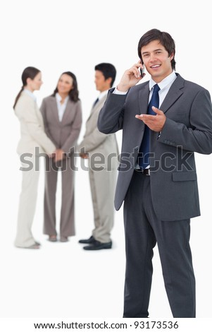 Salesman talking on cellphone with team behind him against a white background