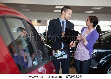 Salesman talking to a smiling woman next to a car in a car shop