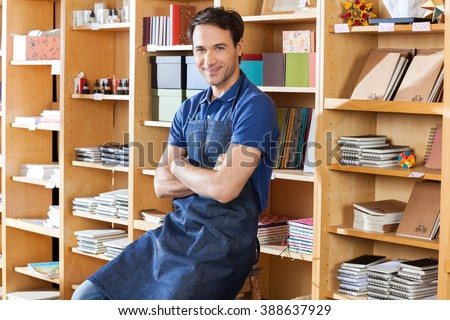 Salesman With Arms Crossed Sitting In Book Store - stock photo