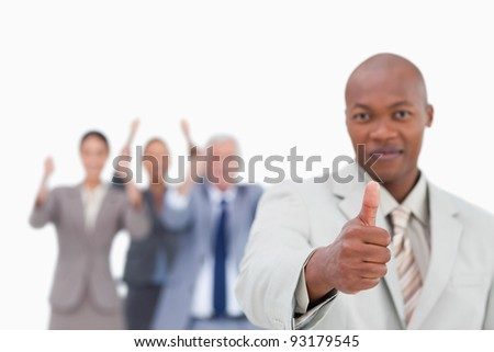 Salesman with team behind him giving approval against a white background - stock photo