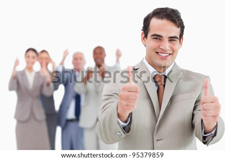 Salesman with team behind him giving thumps up against a white background