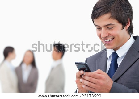 Salesman writing text message with team behind him against a white background - stock photo
