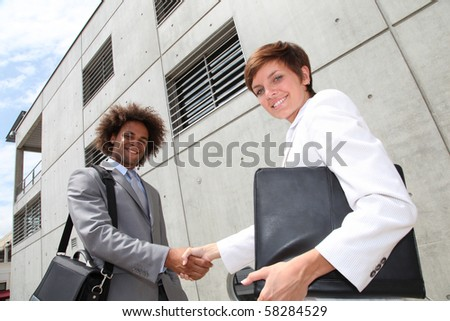 Salespeople shaking hands in front of office building - stock photo