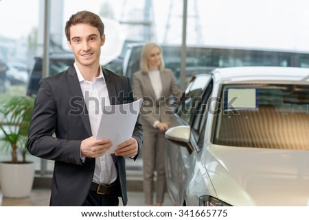 Salesperson on duty. Handsome young male salesperson holding papers while his customer is observing the car.  - stock photo