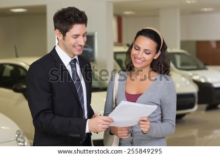 Salesperson showing clipboard to sign to customer at new car showroom - stock photo