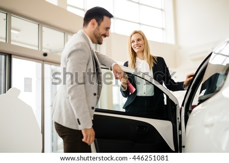 Salesperson showing vehicle to potential customer in dealership - stock photo